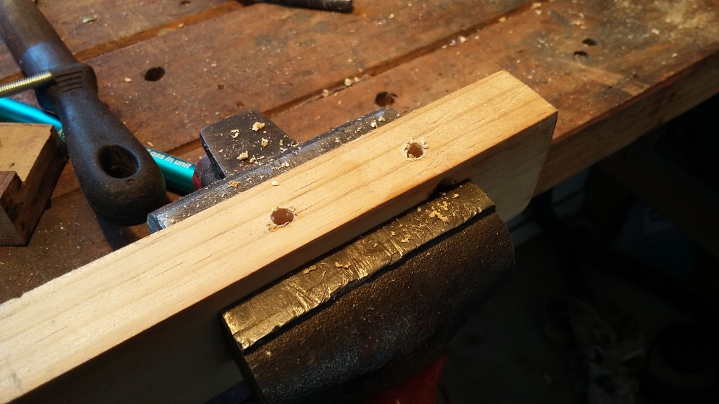 Two holes in the top piece (its upside down at the moment) drilled at the right diameter so the threaded rod can be screwed into the wood and hold tight
